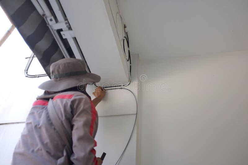 Электрик строительной площадки Работник с электрическими кабелями стоковая фотография rf