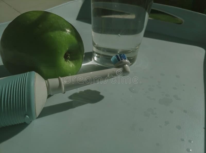 Электрическая зубная щетка с зелеными Яблоком и стеклом воды стоковая фотография