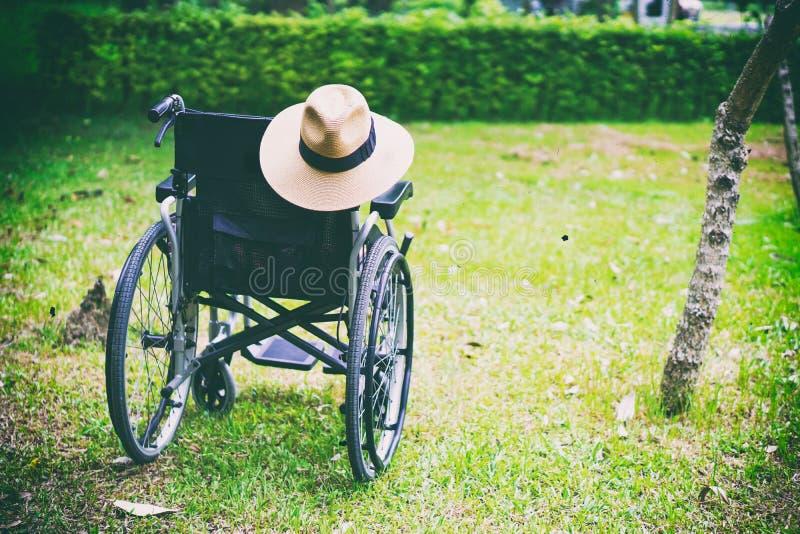 Электрическая кресло-коляска для старого старшего пациента не может идти или вывести люди из строя со шляпой в парке стоковые фото
