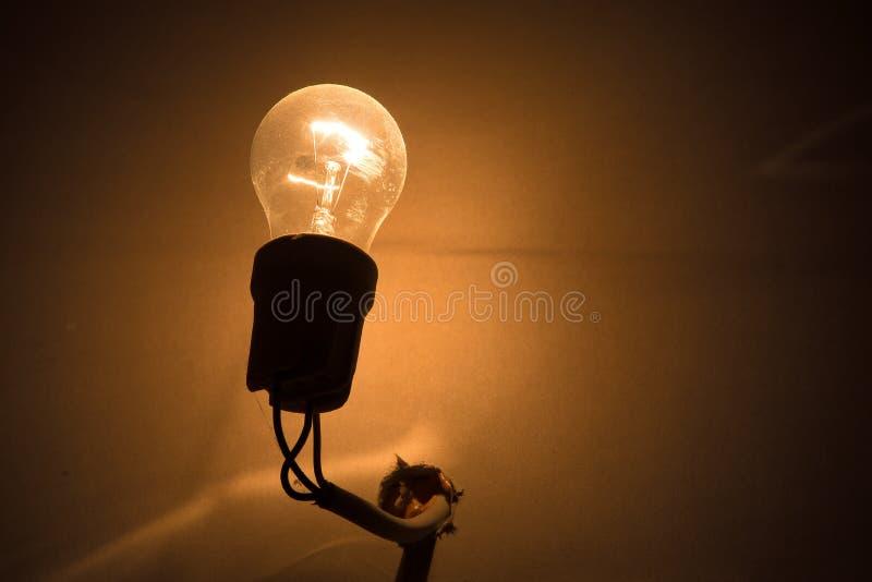 Электрическая лампочка вися на проводе от отверстия на стене стоковое фото