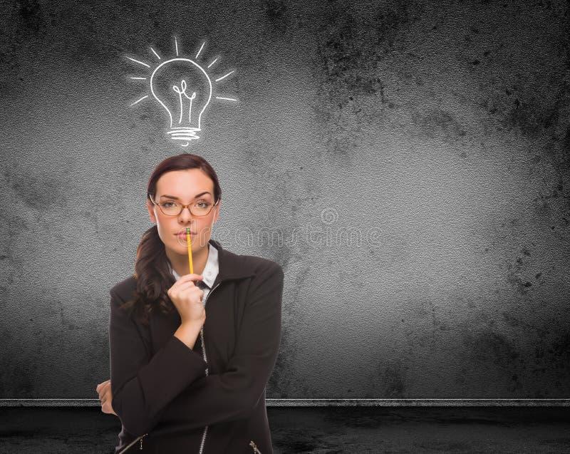 Электрическая лампочка нарисованная над головой молодой взрослой женщины с карандашем перед стеной с космосом экземпляра стоковые фото
