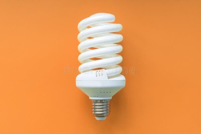 Электрическая лампочка на померанцовой предпосылке Дневной, энергия - сбережения привели лампу стоковая фотография