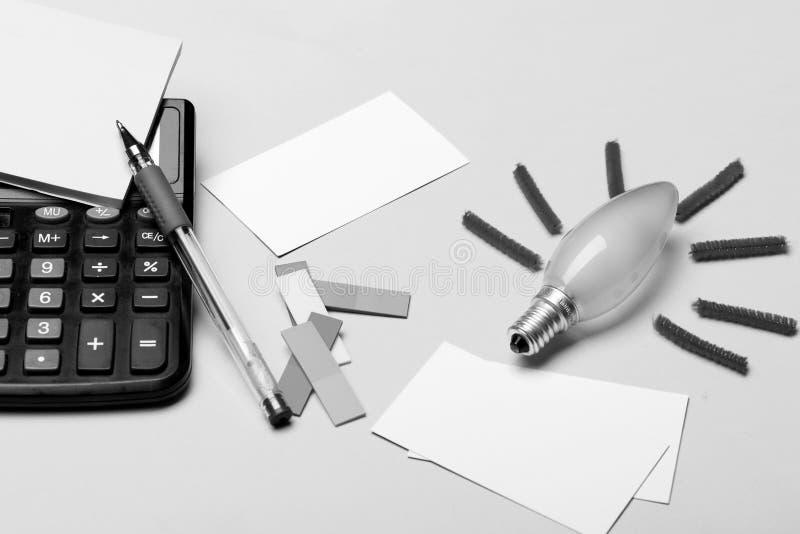 Электрическая лампочка с красными лучами, желтыми бумагами примечания и карточками с ручкой на желтой предпосылке Аксессуары и ид стоковые изображения rf