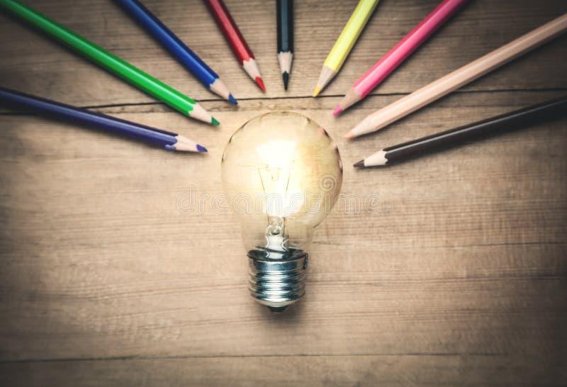 Электрическая лампочка с красочными карандашами на деревянной предпосылке стоковые изображения rf