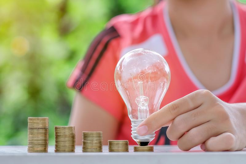 Электрическая лампочка с стогом монеток на деревянном столе в утре Сбережения энергии и денег, бухгалтерия и финансовая концепция стоковые фото