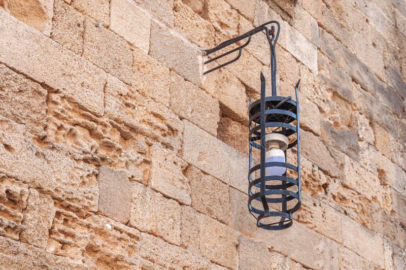 Электрическая лампочка черного листового железа на стене замка желтого цвета блока грубой стоковое фото rf