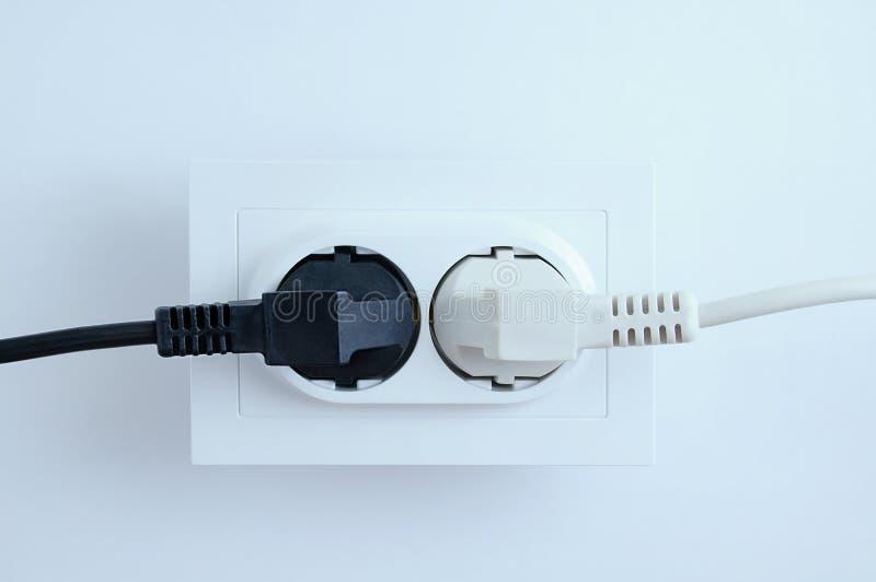 Электрические вилки из электрических приборов, белые и черные, входят в розетку на белом фоне стоковое фото rf