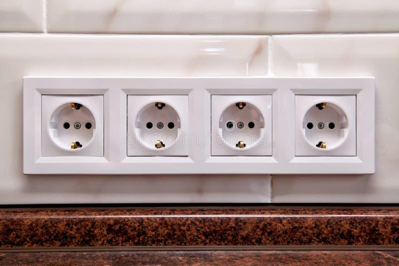Электрические гнезда на стене плитки кухни стоковая фотография rf