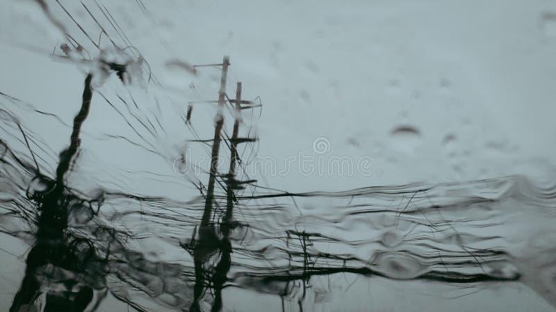 Электрические конкретные поляки с провода когда взгляд от окна автомобиля, голубое небо в дождливом дне стоковые изображения rf