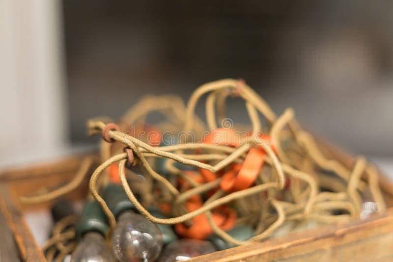 Электрические лампочки внутри желтого крена электрического кабеля на античном деревянном столе стоковые фотографии rf