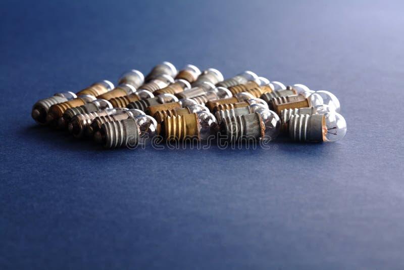 Электрические лампочки установленные на предпосылку голубой бумаги Красочные лампы года сбора винограда бронзы и серебра золота п стоковое фото