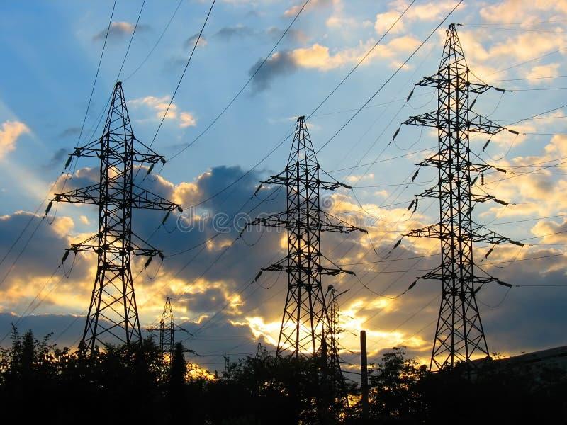 электрические линии приводят передачу в действие захода солнца стоковая фотография rf