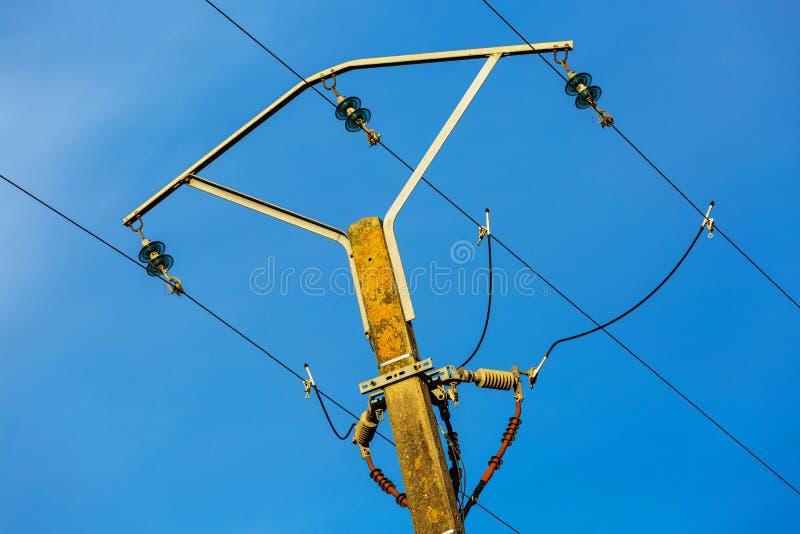 Электрические линии электропередач и провода поляка с голубым небом стоковые изображения