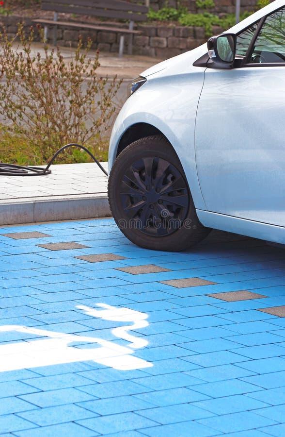 Электрический автомобиль будучи поручанным, с символом штепсельной в стоковые изображения