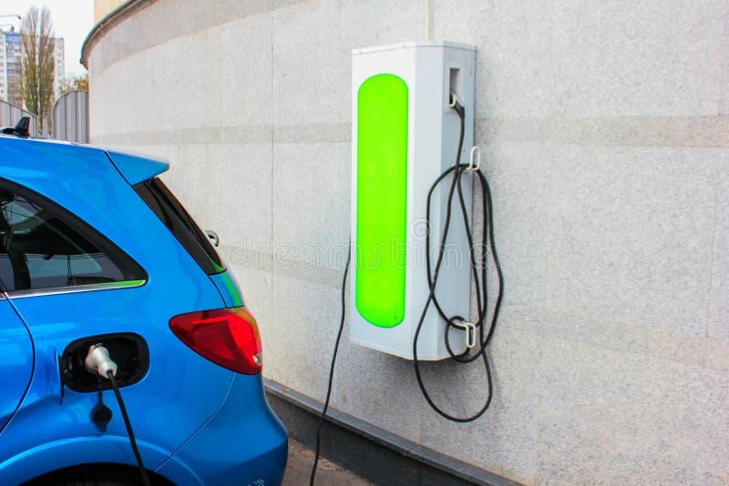 Электрический будучи поручанным автомобиль автомобиль поручая электрическую станцию Закройте вверх электропитания заткнутого в эл стоковое фото rf