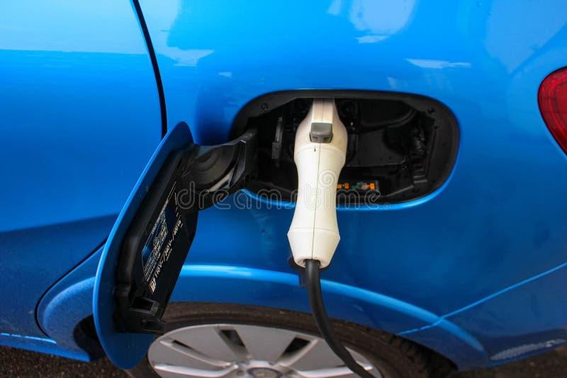Электрический будучи поручанным автомобиль автомобиль поручая электрическую станцию Закройте вверх электропитания заткнутого в эл стоковое фото