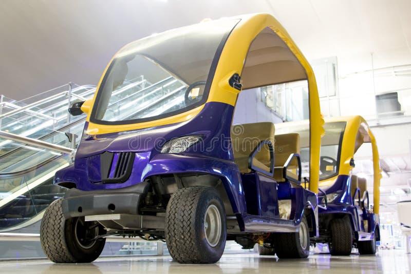 Электрический пассажирский автомобиль припаркованный на авиапорте стоковое фото rf