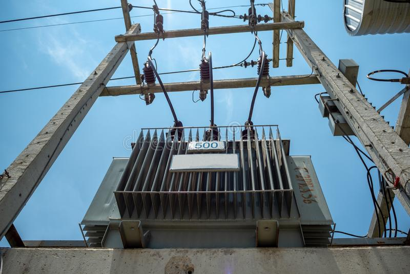 Электрический распределительный трансформатор с высоковольтными кабелями и оборудованием защиты устанавливает на конкретный поляк стоковые изображения