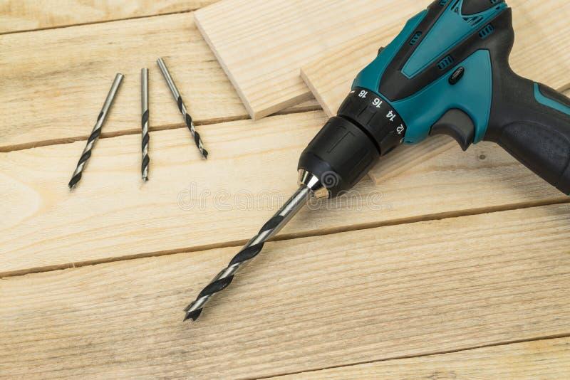 Электрический сверлильный аппарат на деревянной предпосылке Инструменты плотничества стоковая фотография