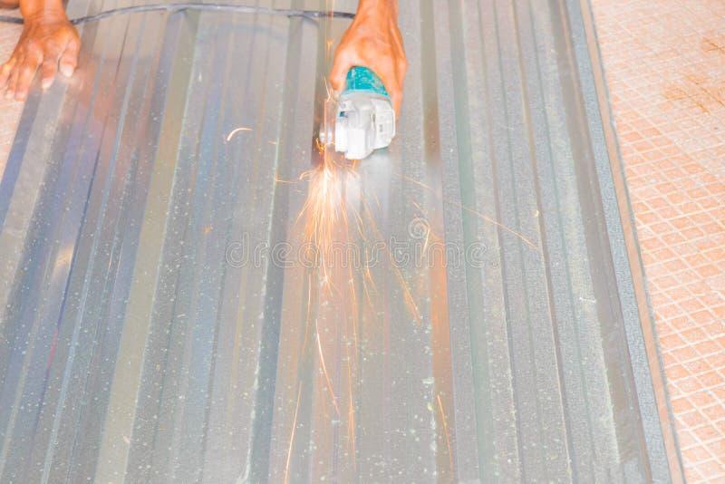 Электрическое колесо меля на крыше листа инструментального металла в конструкторе работает Выберите фокус с малой глубиной поля стоковое изображение rf