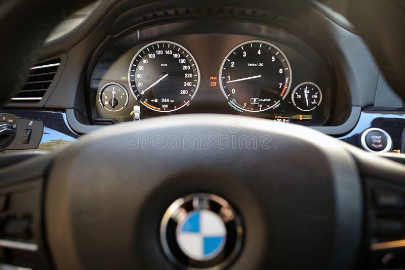 Электронная приборная панель современного роскошного автомобиля BMW 750Li XDrive с колесом из фокуса с логотипом BMW стоковые фото