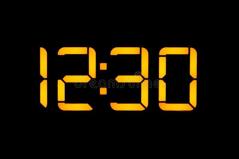 Электронные цифровые часы с желтыми номерами на черной предпосылке показывают времени 12 30 часов дня Изолят, clos стоковые изображения rf