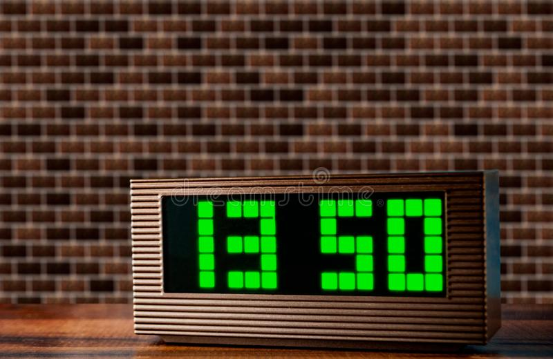 Электронные часы на поверхности на предпосылке кирпичной стены стоковое изображение