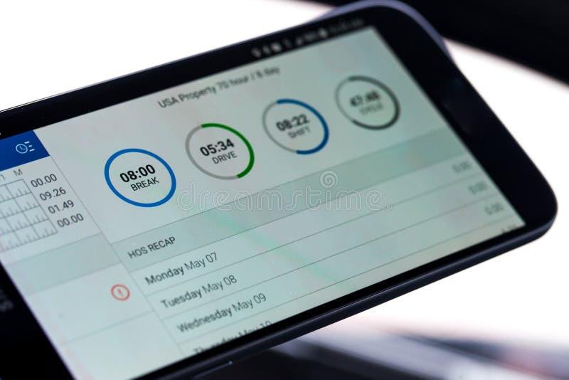 Электронный внося в журнал прибор для грузоперевозок при часы обслуживания показанные на экране smartphone стоковые фото