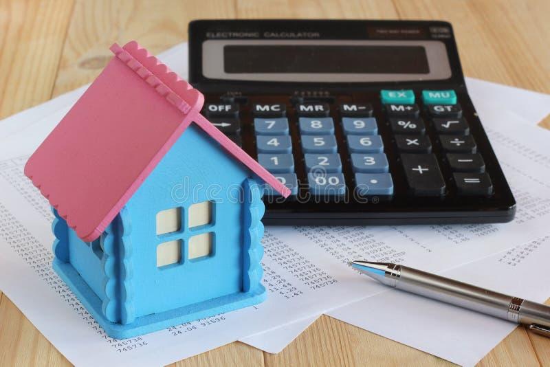 Электронный калькулятор с кнопками, деревянный модельный встреченный дом, стоковая фотография