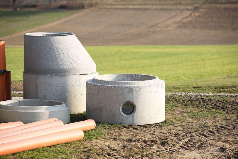 Элементы бетонных конструкций для расположения канализаций лежат на зеленой траве в лучах солнца Стены  стоковая фотография rf