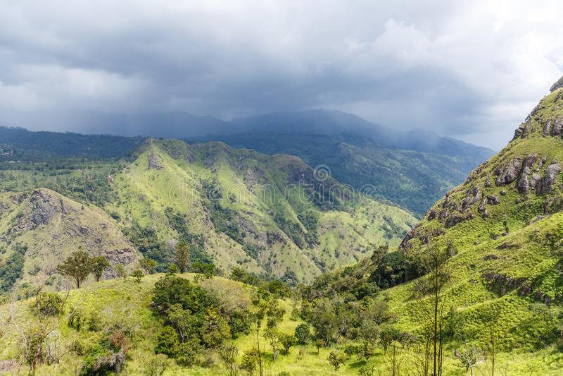 ЭЛЛА, ШРИ-ЛАНКА - 17-ОЕ ЯНВАРЯ 2017: красивый сценарный взгляд гор покрытых с зелеными растениями и облачным небом в Азии стоковое фото