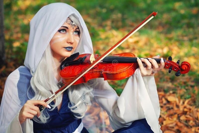 Эльф с скрипкой в лесе осени стоковое изображение