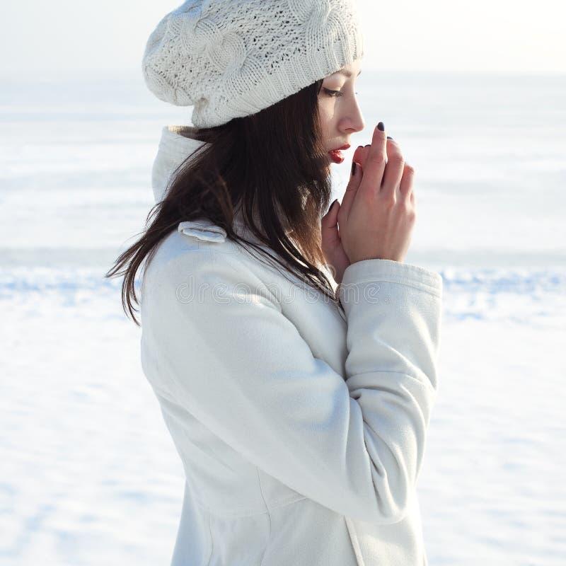 Эмотивный портрет модной модели в белых пальто и берете стоковые изображения