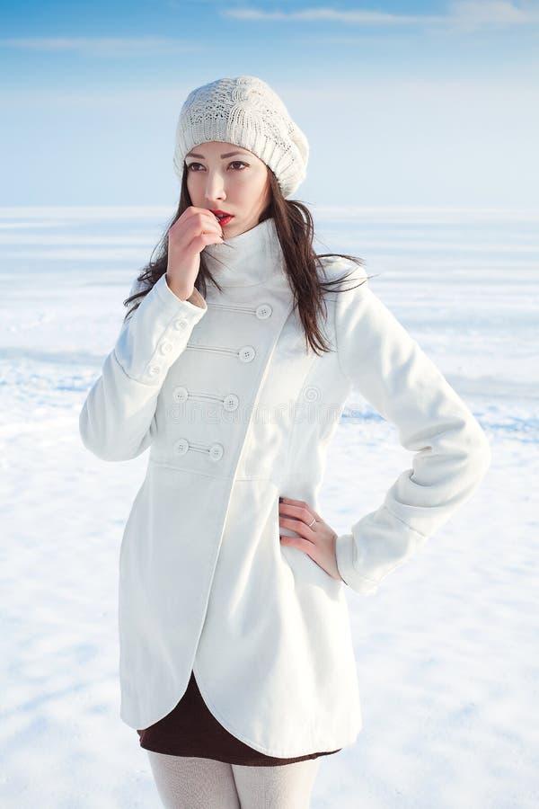 Эмотивный портрет модной модели в белых пальто и берете стоковое фото