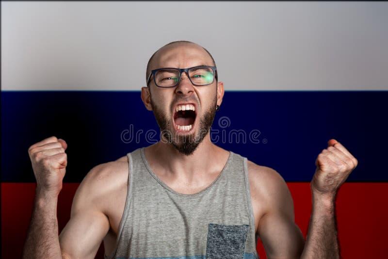 Эмоции гнева и негодования Человек в стеклах обхватил его крикнутые руки в кулаки и На заднем плане флаг  стоковые изображения