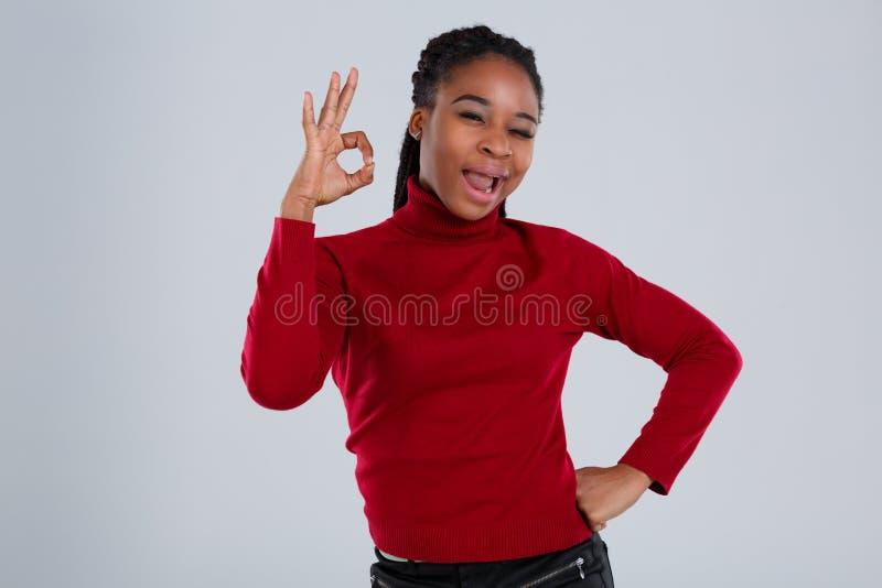 Эмоциональная афро американская девушка показывая сторону жеста одобренную и гримасничая стоковая фотография rf