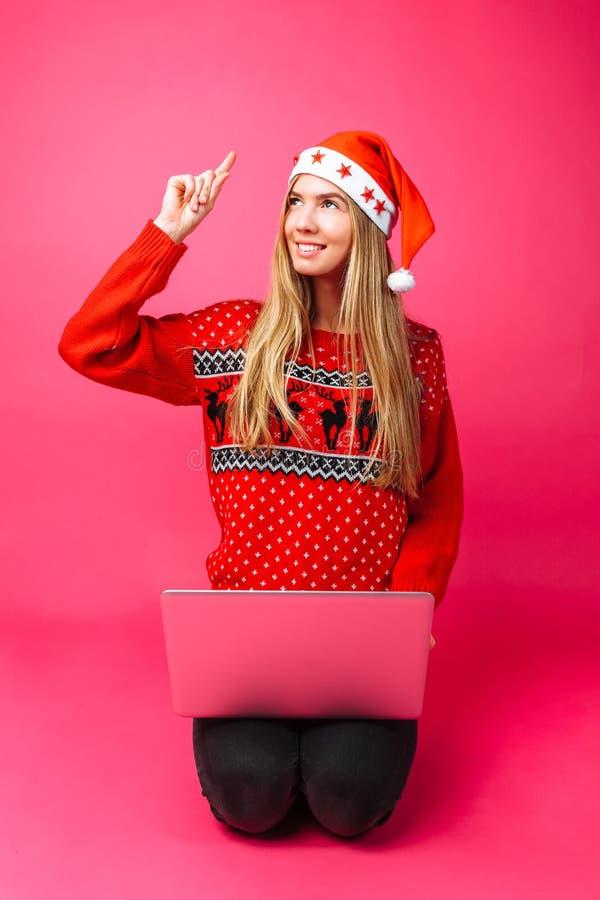 Эмоциональная девушка в красных свитере и шляпе Санты, сидя с a стоковое изображение