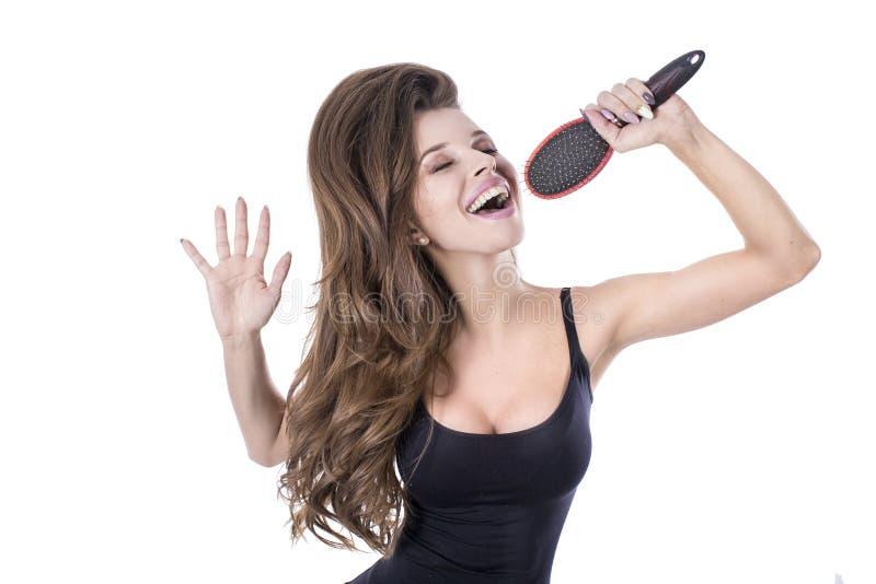 Эмоциональная девушка поя в щетке для волос на белой предпосылке Концепция здоровья Hait стоковые изображения