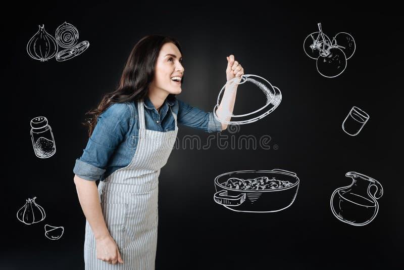 Эмоциональная домохозяйка усмехаясь пока варящ ужин стоковое изображение rf