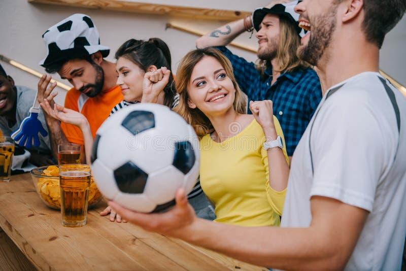эмоциональная многокультурная группа в составе друзья наблюдая футбольный матч стоковое изображение