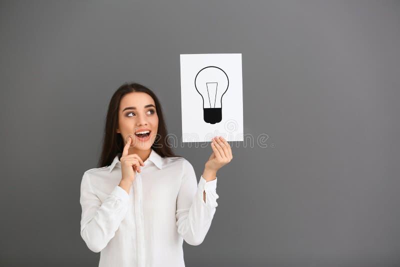 Эмоциональная молодая женщина держа лист бумаги с вычерченной электрической лампочкой как символ идеи на серой предпосылке стоковая фотография rf