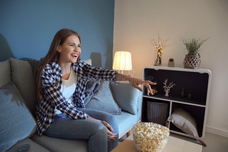 Эмоциональная молодая женщина есть попкорн пока смотрящ ТВ поздно в вечере стоковые изображения
