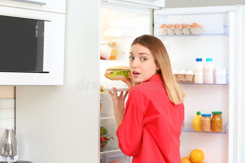 Эмоциональная молодая женщина принимая сэндвич от холодильника в кухне стоковые изображения rf