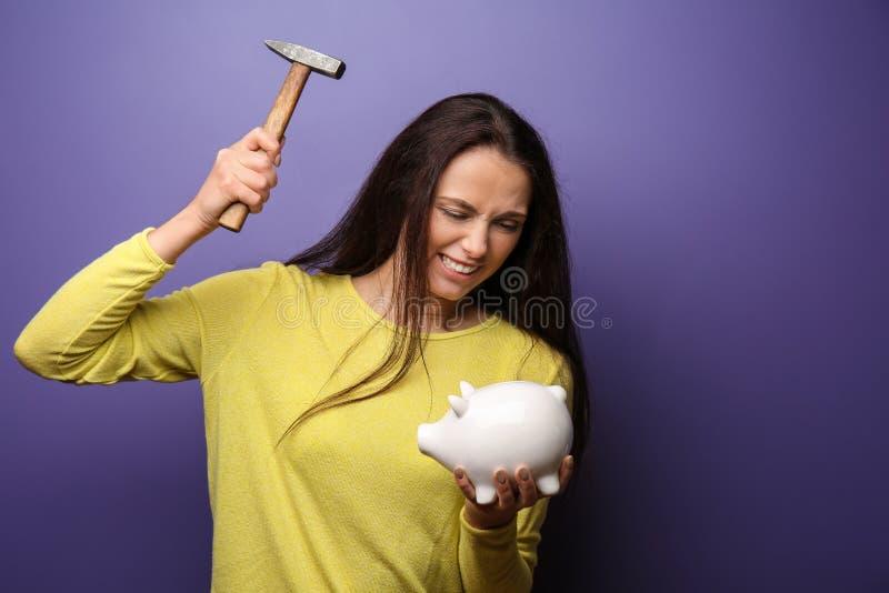 Эмоциональная молодая женщина пробуя сломать копилку с молотком на предпосылке цвета стоковое фото rf