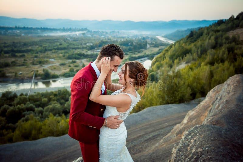 Эмоциональная свадьба снятая новобрачных Счастливая пара усмехающся и обнимающ на предпосылке красивого ландшафта стоковые изображения