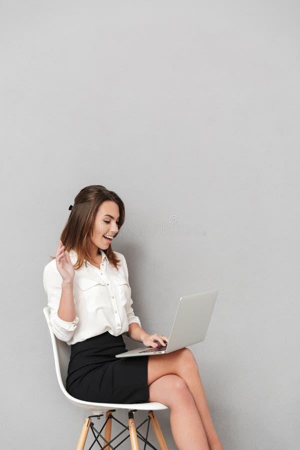 Эмоциональная счастливая молодая бизнес-леди используя портативный компьютер развевая к друзьям стоковые фотографии rf