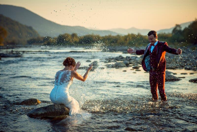 Эмоциональные внешние пары новобрачных портрета свадьбы счастливые красивые усмехаясь играя брызгающ воду имея заход солнца потех стоковая фотография rf