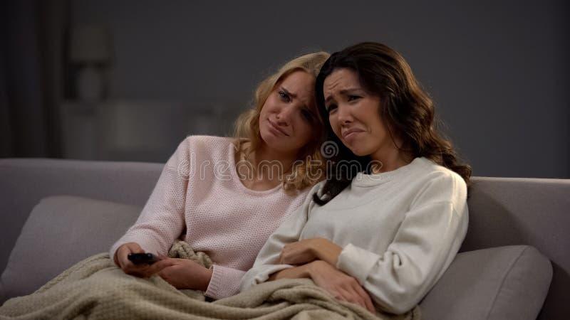 Эмоциональные красивые девушки наблюдая мелодраму и плакать, сидя на софе дома стоковая фотография