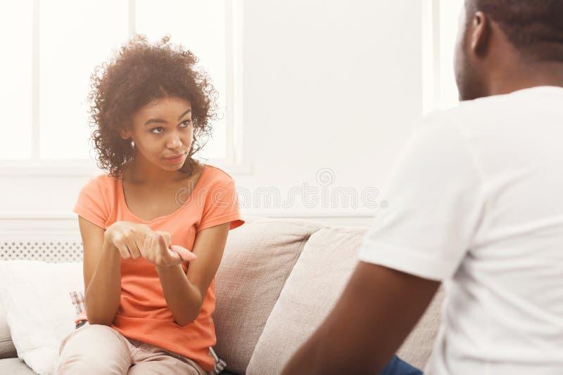 Эмоциональные черные пары говоря на софе дома стоковое фото