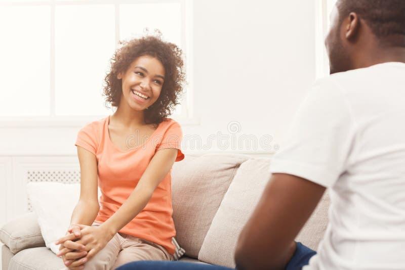 Эмоциональные черные пары говоря на софе дома стоковые фотографии rf
